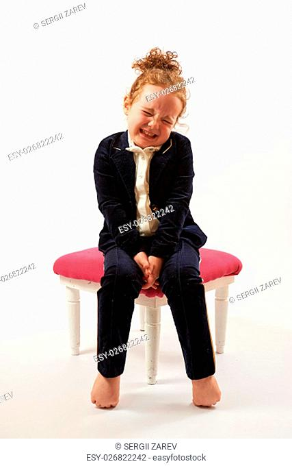 Little girl in black suit sitting on a rose stool
