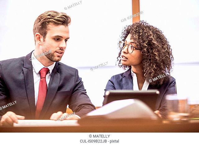 Young businesswoman and businessman brainstorming at boardroom table