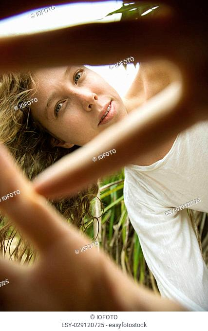 Low angle view of Caucasian young adult woman holding hands out to camera and peeking through fingers