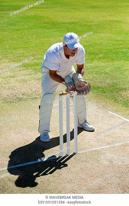 High angle view of wicketkeeper standing behind stumps on field
