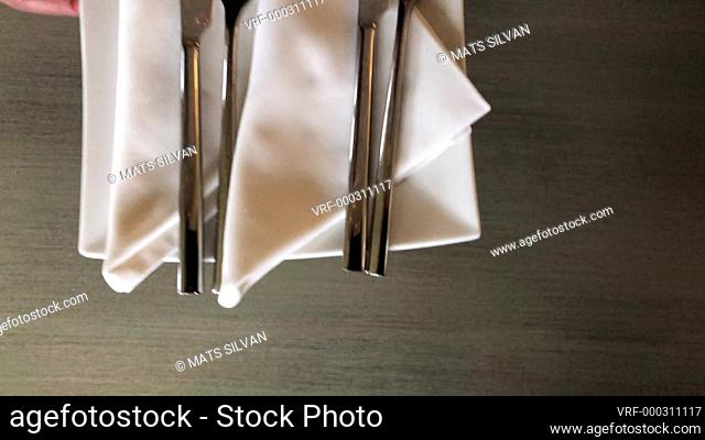 Woman Hand Putting Eating Utensils on the Table