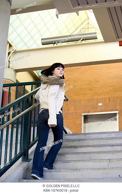 Portrait of a young woman climbing up a flight of stairs