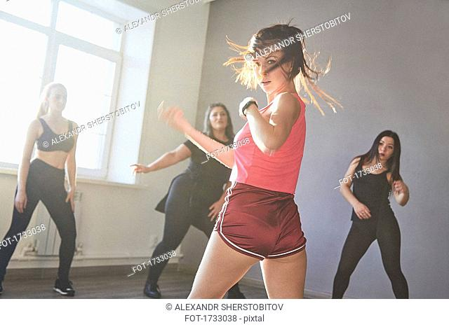 Confident female dancing while women looking at studio on sunny day