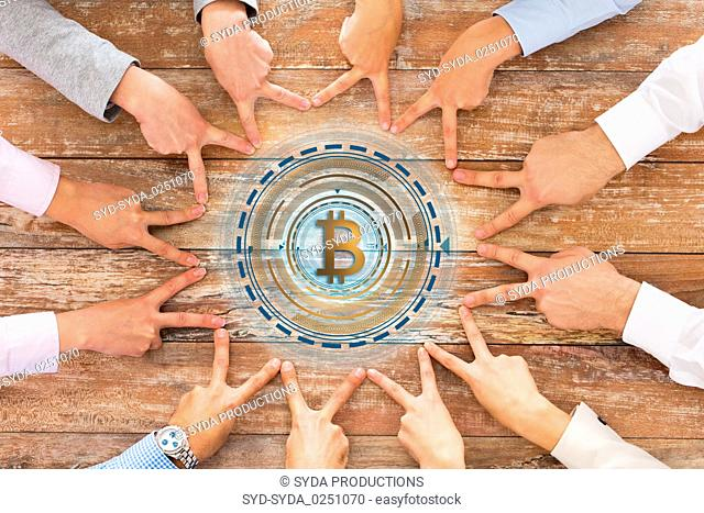 business team showing peace hand sign with bitcoin