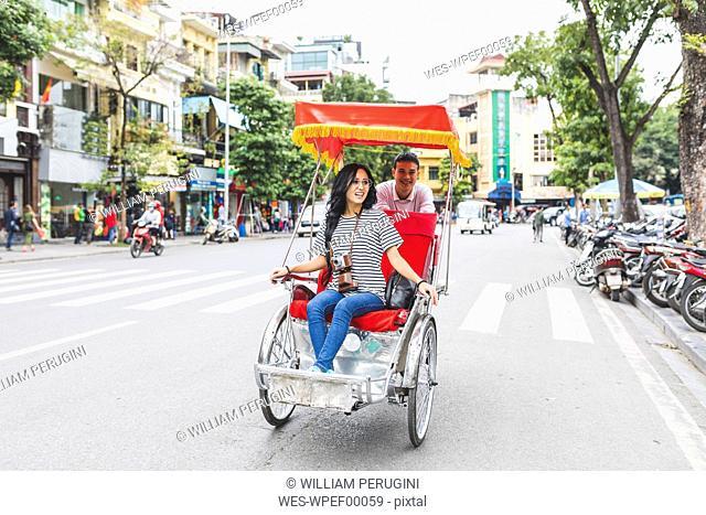 Vietnam, Hanoi, young woman on a riksha exploring the city