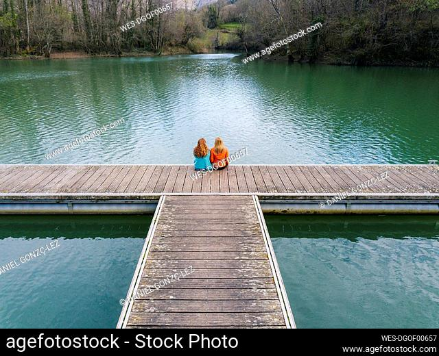 Back view of two friends sitting side by side on jetty, Valdemurio Reservoir, Asturias, Spain
