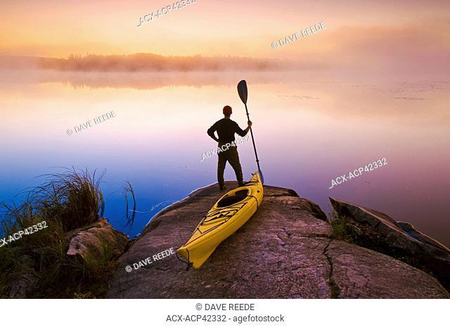 Man with kayak,Bunny Lake, near Sioux Narrows, Northwestern Ontario, Canada