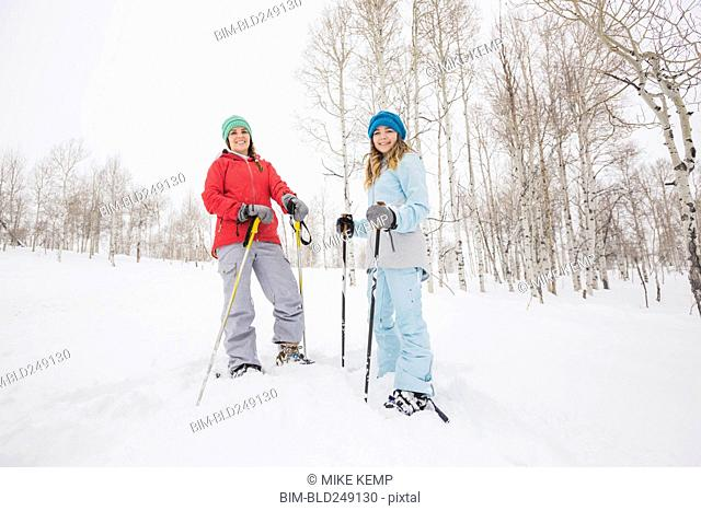 Portrait of Caucasian mother and daughter snowshoeing