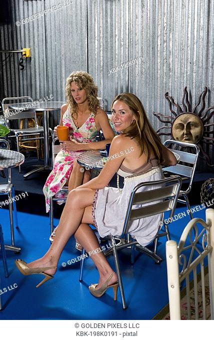 Two young women enjoying beverage in a cafi