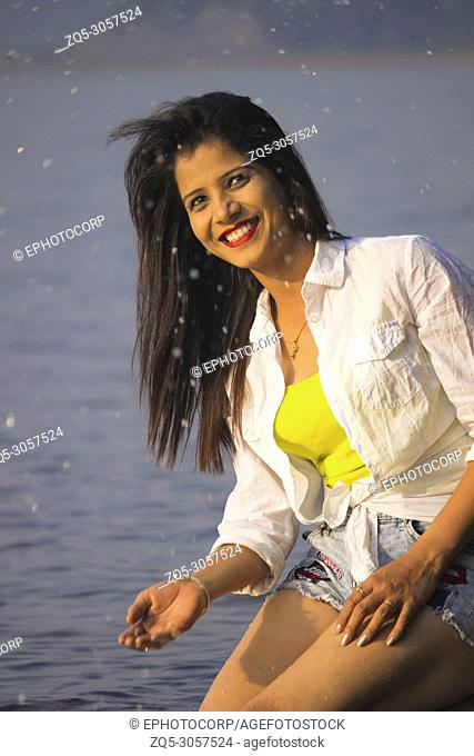 Smiling woman in yellow top, white jacket and denim shorts with water drops on face