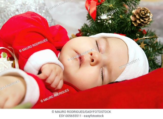 View of a newborn baby on a Christmas suit sleeping