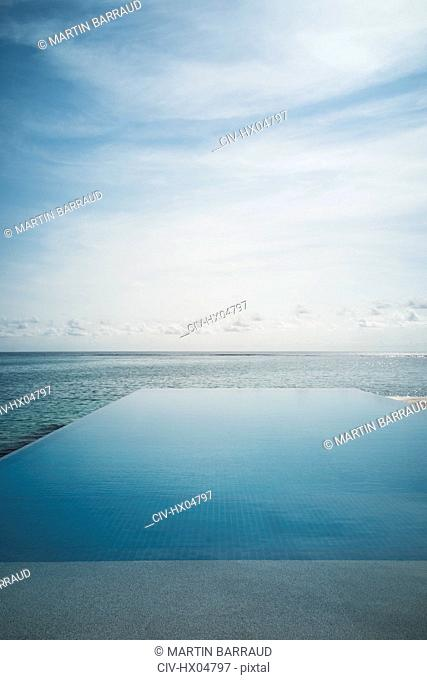 Tranquil blue infinity pool and ocean, Maldives, Indian Ocean