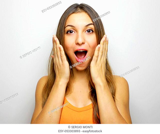 Woman happy and surprised shouts holds cheeks by hand. Beautiful girl with orange tank top excited on white background. Expressive facial casual woman