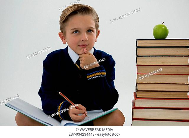 Schoolboy doing his homework while sitting beside books stack