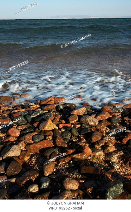 View of the ocean across the pebbles as the sun begins to set Dahab Egypt