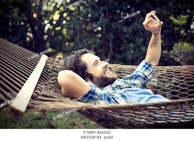 A man lying in a garden hammock taking selfies with his phone