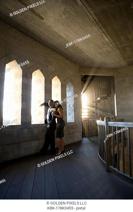 Young couple in formal attire looking out window of medieval castle