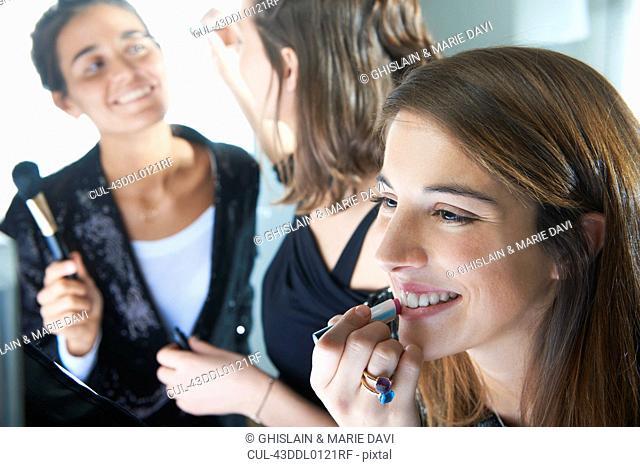 Women applying make up together