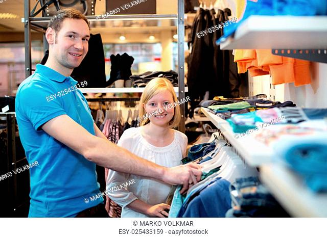 young couple in the clothes shop looking for a new dress