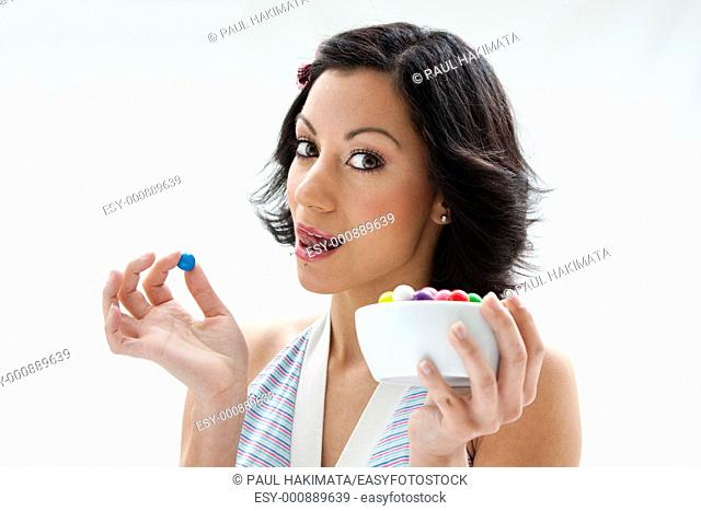 Happy beautiful candy girl with a bowl of colorful bubblegum candy balls licking her lip, isolated