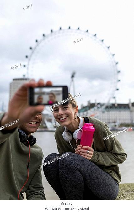 UK, London, two runners taking a selfie at riverwalk