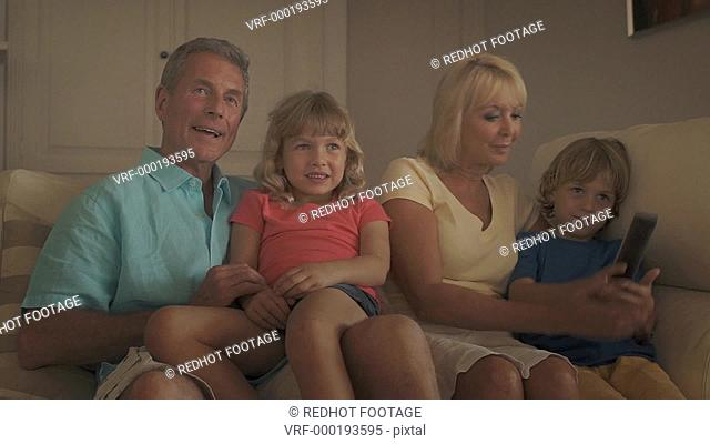 Grandparents and grandchildren in living room watching television on sofa