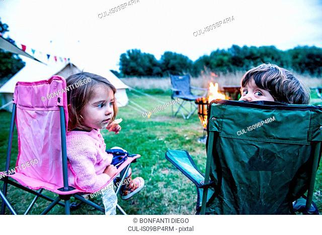 Children relaxing in front of bonfire