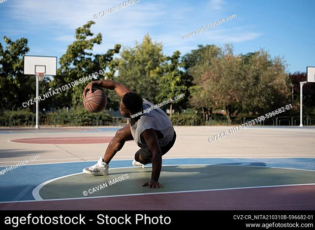 Muscular African American player doing freestyle dribbling on court