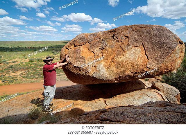 Man at Devil's Marbles rock in Australia