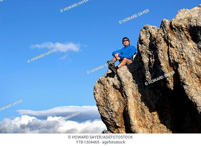 Man sitting on a rock ledge