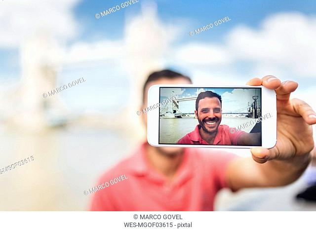 UK, London, tourist taking a selfie with the Tower Bridge