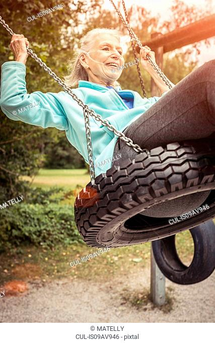 Senior woman swinging on tyre swing looking away smiling