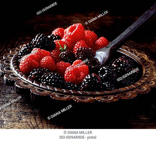 Succulent, juicy, fresh raspberries and blackberries on carved ornamental plate