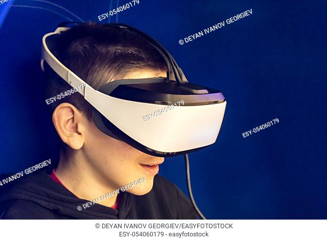 Child watching movie with VR glasses. Blue illuminated cabin with joysticks. Special effects. Technology and entertainment concept with virtual reality glasses