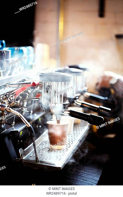 Specialist coffee shop. A person working at a large coffee machine, with three percolating coffee dispensers, handles and a pipe sending out steam