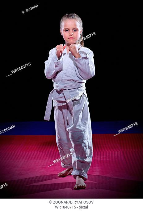 Little girl aikido fighter on black
