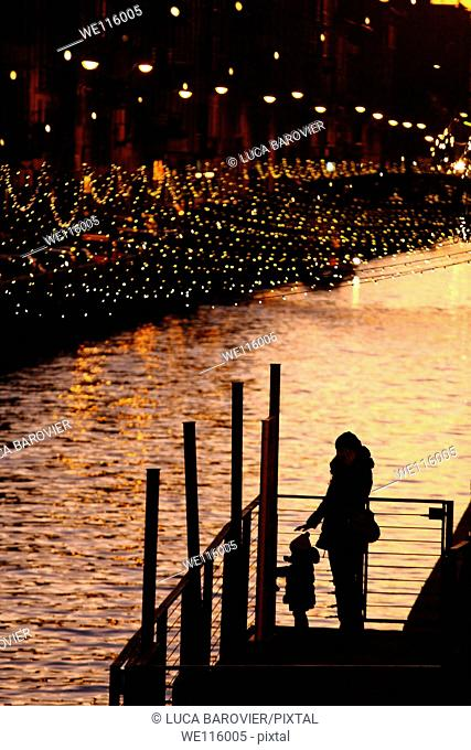 Mother and son silhouette on the Naviglio Grande, Milan Italy