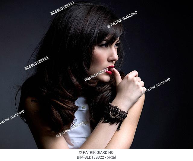 Mixed Race woman biting on thumb