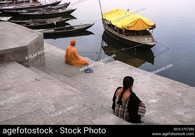 Varanasi, Uttar Pradesh, India, Asia - Two people sit at a ghat on the banks along the holy Ganges and look at the river