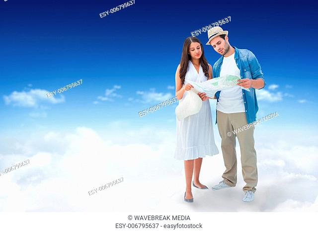 Composite image of lost hipster couple looking at map