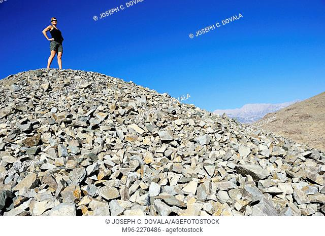 Woman stands on tailing pile of old gold mine, Alabama Hills, California, USA
