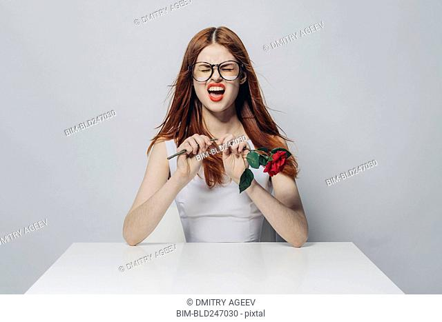 Caucasian woman sitting at windy table snapping stem of rose