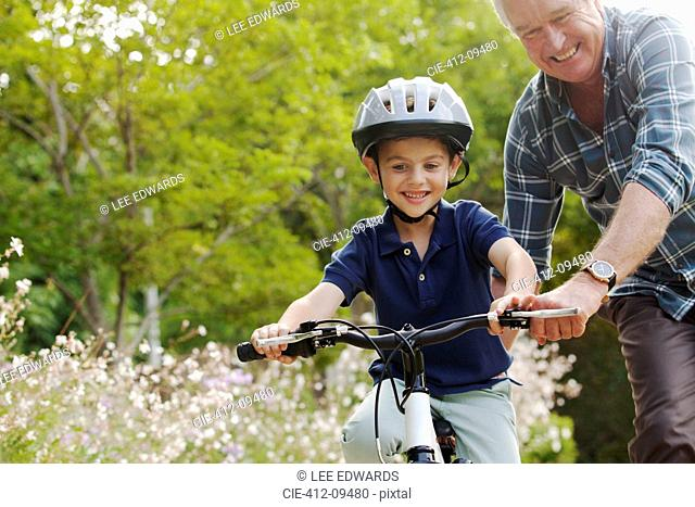 Grandfather teaching grandson to ride bicycle