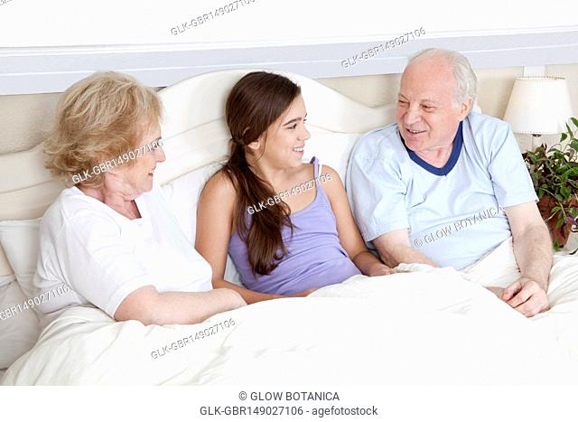 Family lying in the bed and smiling
