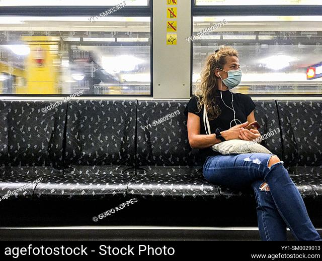 Berlin, Germany. Young afult woman commuting by U-Bahn while wearing a mandatory facemask to prevent the Covid-19 Virus the spread further during the 2020...