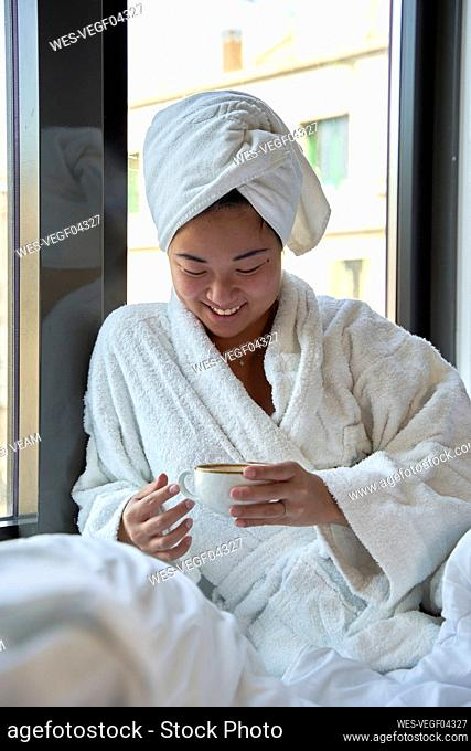 Smiling woman holding coffee cup in hotel