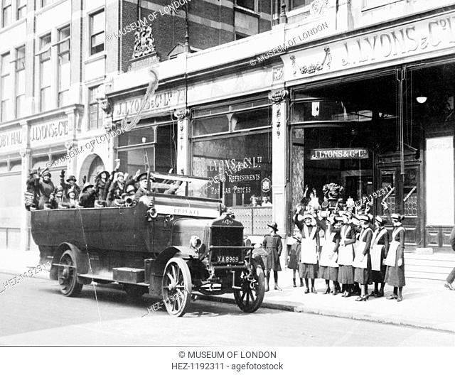 Lyons shop, Fulham Broadway, Fulham, London. A private bus is parked outside, with a group of women waving to a crowd of Lyons' waitresses standing on the...
