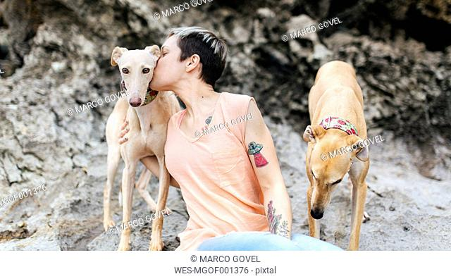 Spain, Llanes, young woman with her greyhounds on the beach