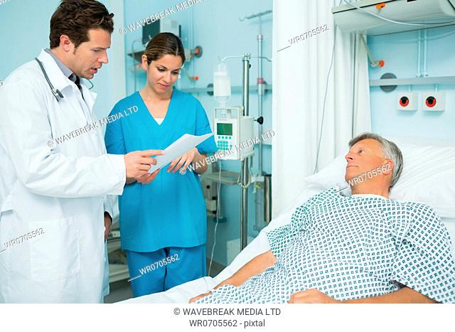 Doctor and nurse looking at a paper with a patient in a hospital