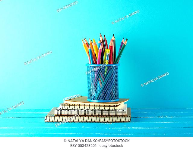 metal blue stationery stand with multi-colored wooden pencils on a blue background, concept back to school